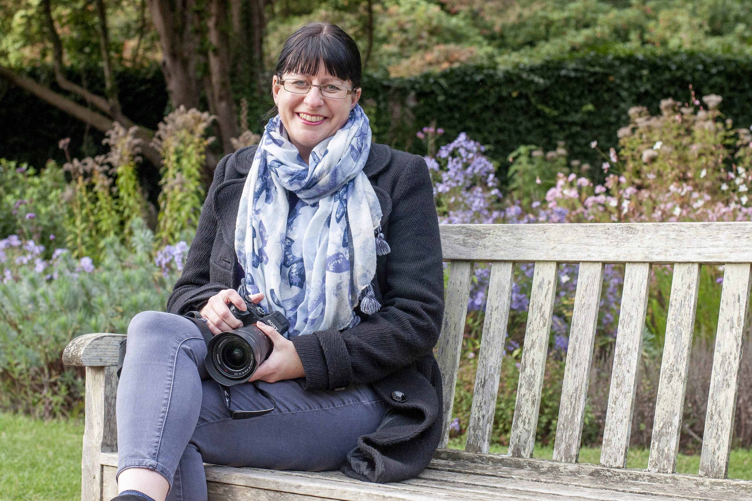 Photo of Jane Mucklow with camera, sitting on a bench at Scotney Castle
